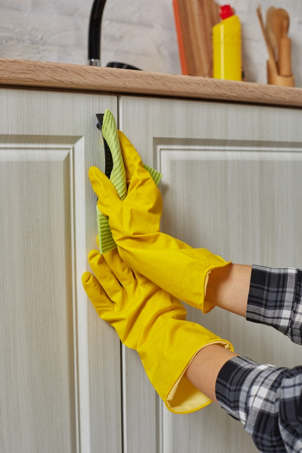 Cleaning Greasy Kitchen Cabinets. Woman wearing clothes cleaning cabinet handles