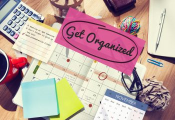 Organization tips- a desk full of papers, sticky pads, a calculator, coffee mug, and a calendar