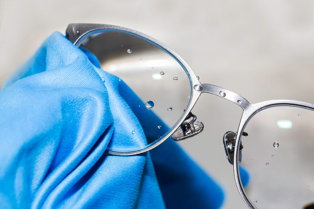 A pair of silver eyeglasses getting cleaning with a cleaning solution and a blue cloth.