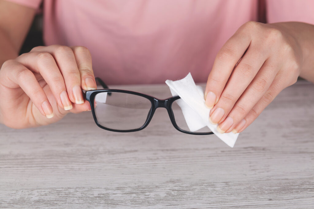 A woman cleaning a pair of eyeglasses.